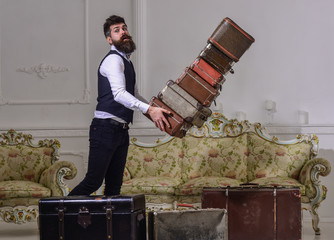 Macho elegant on careless face drops pile of vintage suitcases. Butler and service concept. Man with beard and mustache wearing classic suit delivers luggage, luxury white interior background.