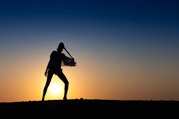 Silhouette of African girl on hill top posing and dancing with sunset view and ocean view.