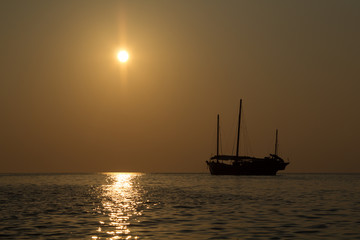 Wooden junk sail boat in the setting sun