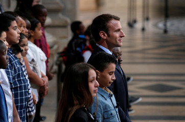 French President Emmanuel Macron stands with children at the Pantheon in Paris, to pay homage to victims of the slave trade and to commemorate 170 years since the abolition of slavery in its colonies