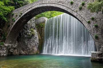 Traditional stone bridge and waterfall near Paleokaria village in Thessaly, Greece