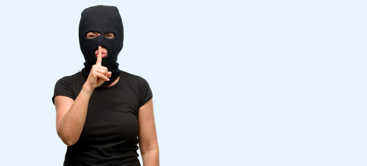 Burglar terrorist woman wearing balaclava ski mask with index finger on lips, ask to be quiet. Silence and secret concept isolated blue background