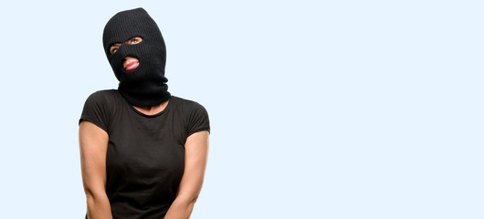 Burglar terrorist woman wearing balaclava ski mask thinking and looking up expressing doubt and wonder isolated blue background - fototapety na wymiar
