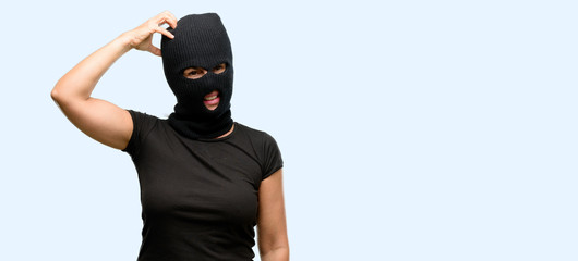 Burglar terrorist woman wearing balaclava ski mask doubt expression, confuse and wonder concept, uncertain future isolated blue background