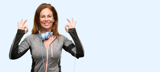 Middle age gym fit woman with workout headphones doing ok sign gesture with both hands expressing meditation and relaxation isolated blue background