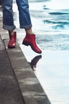 woman with red short boots standing on sidewalk next to a puddle of rain
