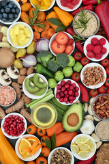Food for healthy eating with fresh vegetables, fruit, herbs, spices, grains, nuts and seeds, forming a background. Foods very high in antioxidants, anthocyanins, minerals and vitamins.