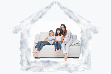 Mother with their children sitting on sofa against house outline in clouds