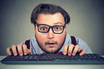 Surprised business man typing on key board
