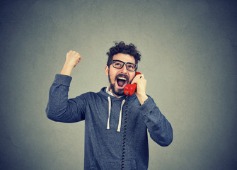 hipster man receiving great news by phone feeling excited