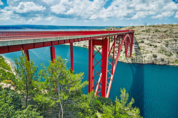 Maslenica bridge. A red bridge connecting two banks. White clouds in the sky and blue sea.