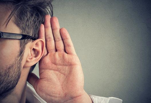 man holds his hand near ear and listens carefully