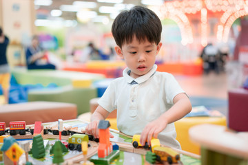 A boy is playing the city toys.