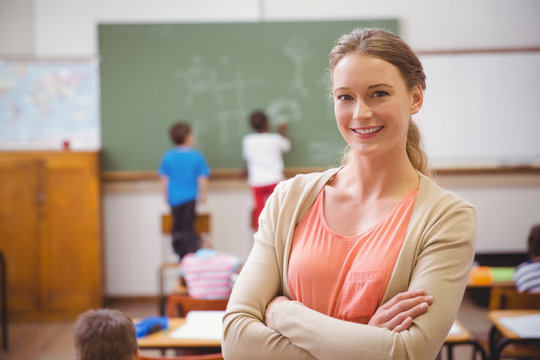 Pretty teacher smiling at camera at back of classroom