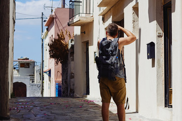 Traveller with camera and backpack takes pictures of the foreign city during the vacation, Crete, Greece