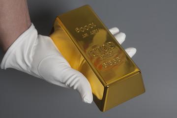 Men's hand in white gloves holding a gold bullion