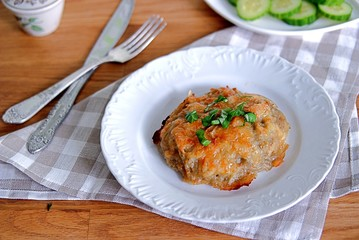 Baked grated potato with fish filling, sprinkled with cheese