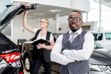 African man in glasses standing against a girl checking the car in the showroom