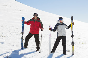 Full length of a couple with ski boards on snow