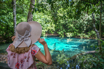 Female Tourist in Hat Looking at Sra Morakot Blue Pool at Krabi Province in Thailand. Caucasian Woman Visiting Famous Natural Attraction in Krabi