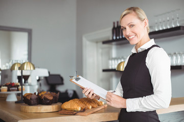 Smiling waitress with clipboard standing at counter
