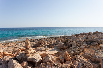 Cap de Ses Salines, Mallorca - The famous orange pebble stone at the beach of Ses Salines