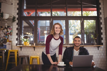 Portrait of smiling man and woman with laptop at coffee shop