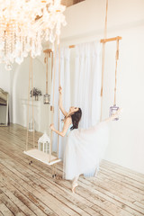Young pretty ballerina is dancing near swing in studio with light interior and wooden floor