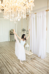 Young pretty ballerina is wearing white skirt dancing near swing in studio with light interior and wooden floor