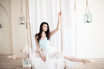 Young beautiful ballerina is sitting on twine in studio with light walls