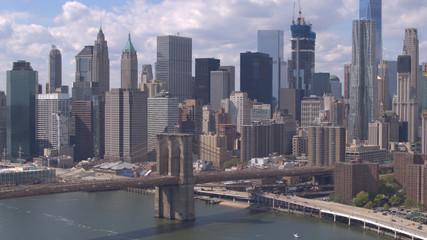 AERIAL: Famous Brooklyn Bridge against Lower Manhattan downtown cityscape