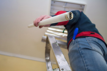 Electrician man worker in uniform installing ceiling fluorescent lamp