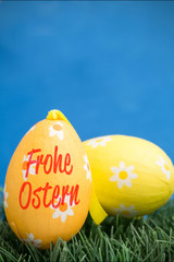 frohe ostern against two easter eggs on grass