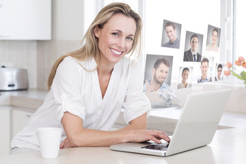 Happy woman using laptop at counter against profile pictures
