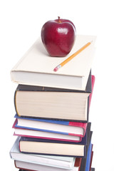 Stack of books with apple and pencil isolated