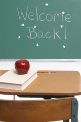 Desk, books and an apple on top of a school desk in a classroom with spit balls on the chalkboard