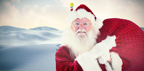 Jolly Santa carries his sack against digitally generated snowy landscape with pole