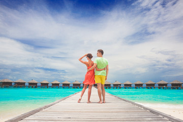 happy young couple walking on wooden bridge by the beach. Maldives
