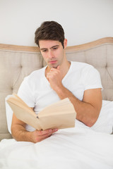 Relaxed man reading book in bed