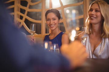 Smiling beautiful woman having glass of champagne in restaurant