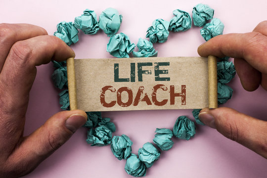 Word writing text Life Coach. Business concept for Mentoring Guiding Career Guidance Encourage Trainer Mentor written on Cardboard Paper Holding by man plain background on Heart Paper Balls.