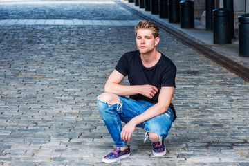 Portrait of Young American Man with little beard in New York, wearing black T shirt, blue destroyed  jeans, fashionable shoes, squatting on brick ground of vintage street, thinking, lost in thought..