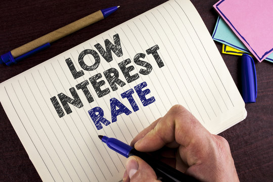 Conceptual hand writing showing Low Interest Rate. Business photo showcasing Manage money wisely pay lesser rates save higher written by Man on Notebook Book on wooden background Pen.