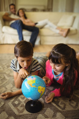 Siblings lying and looking at globe in living room