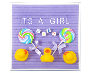 Purple display board with white letters spelling It's a Girl, blocks spelling baby, surrounded by swirled colorful lollipops and yellow rubber duckies. New baby theme. Isolated on white.