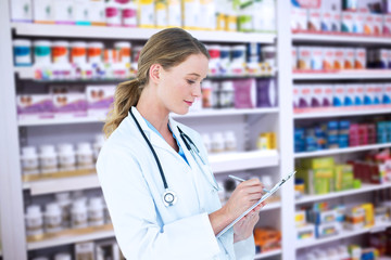 Doctor writing on clipboard against close up of shelves of drugs