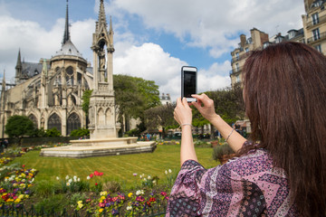 Woman taking photo with cell phone at Notre-Dame in Paris, France
