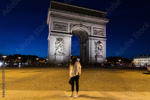 a woman at arc de triomphe in paris france at night stock photo