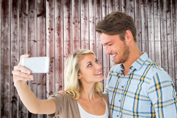 Attractive couple taking a selfie together against wooden planks