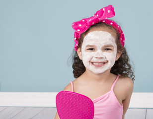 Smiling, little girl in white face mask isolated on blue background